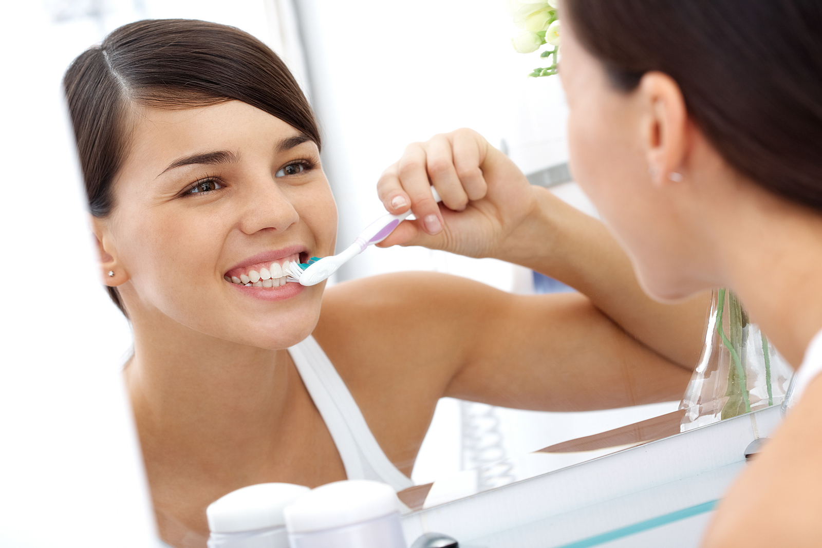Girl brushes her teeth in the mirror while smiling.